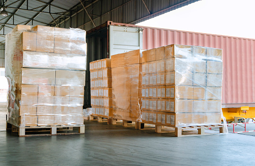 Stack of cardboard boxes on pallet at distribution warehouse for load into container
